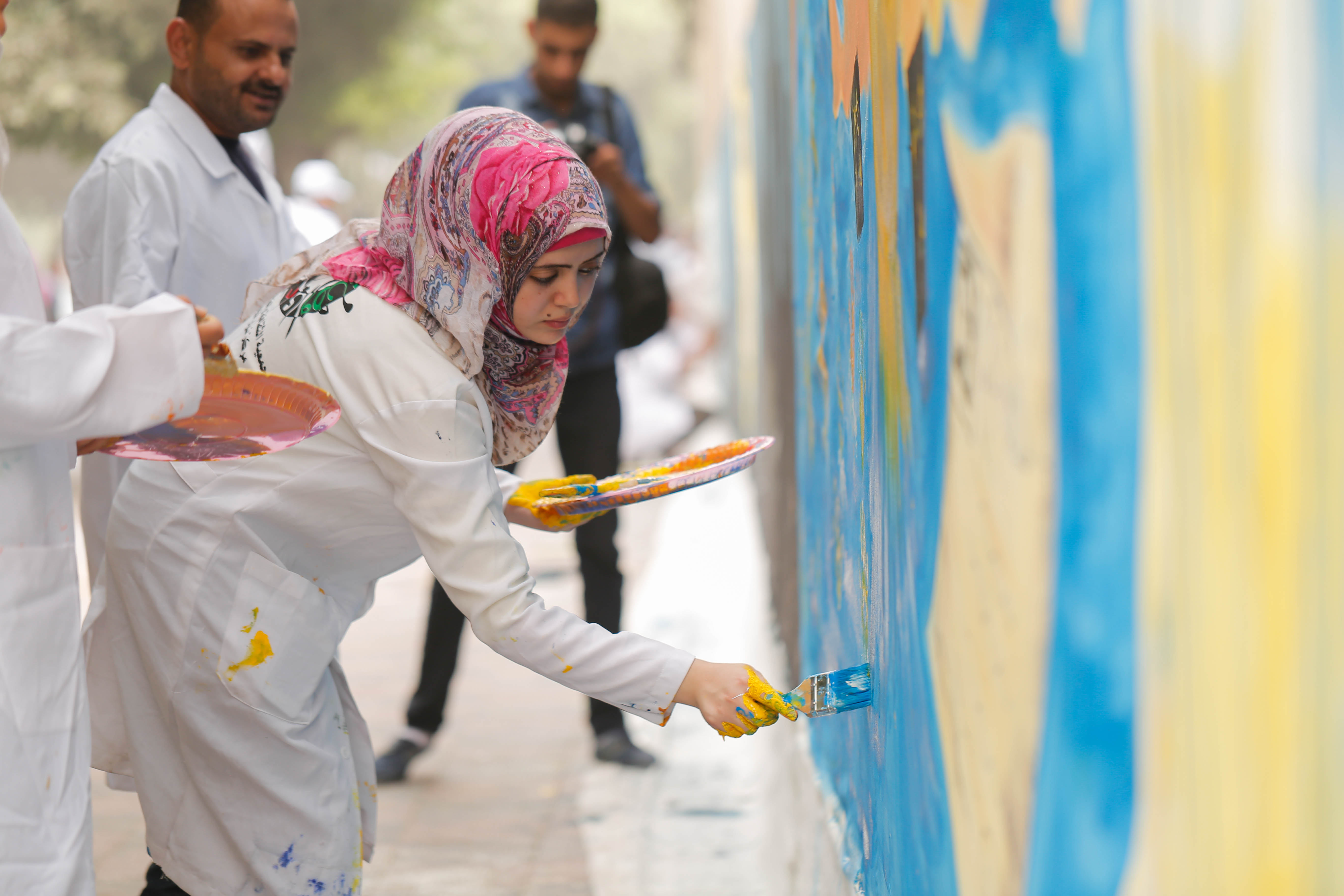 Young Palestinian women and men painting the largest mural in Palestine during the 2015 International Youth Day